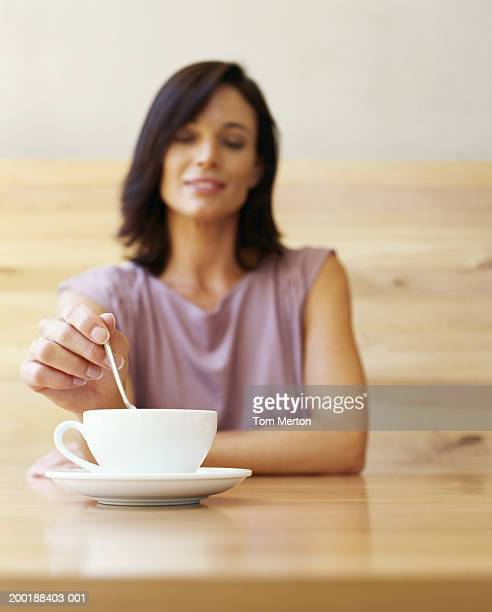 Woman sitting at table stirring cup with spoon, smiling