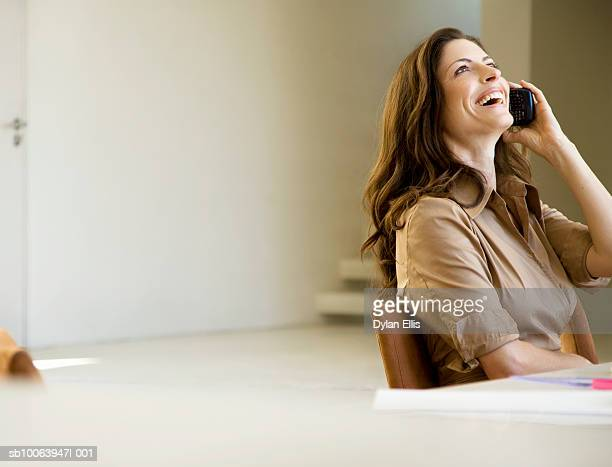 Woman sitting at table talking on PDA, looking away