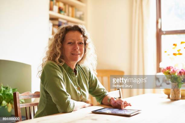 Woman sitting at table using digital tablet
