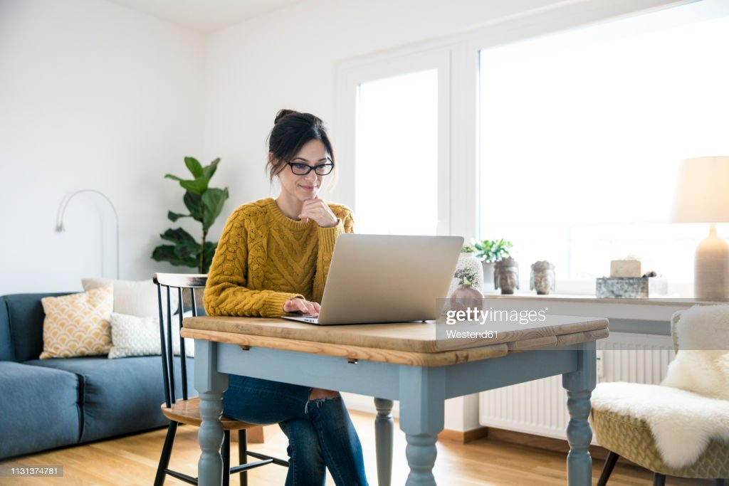 Woman sitting at table, using laptop : Photo