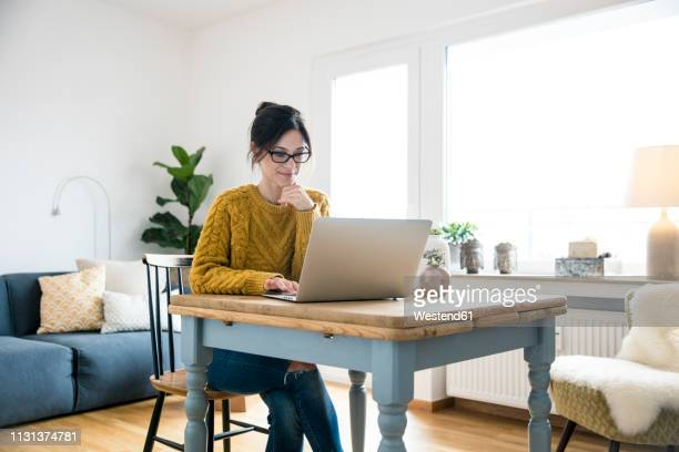 woman sitting at table, using laptop - computer foto e immagini stock