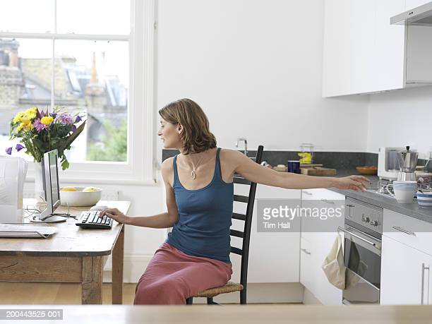 woman sitting at table using pc and reaching for mug - seulement des adultes photos et images de collection