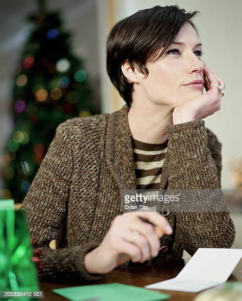 woman sitting at table with  card, resting chin on hand - thinking of you card stock pictures, royalty-free photos & images