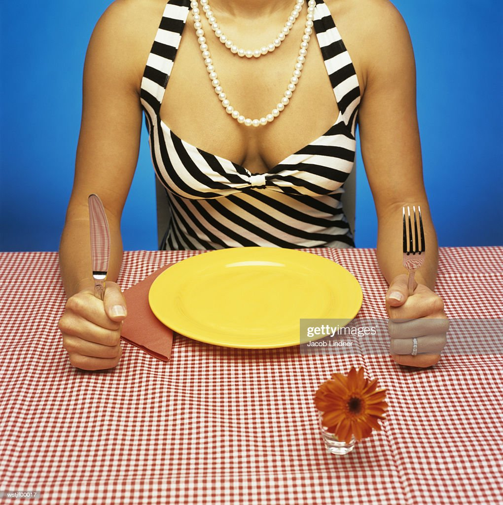 Woman sitting at table with empty plate, holding cutlery : Stock Photo