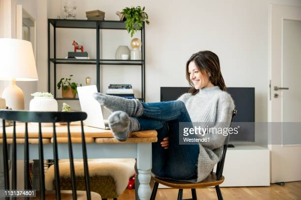 woman sitting at table with feet up, using laptop - feet up stock pictures, royalty-free photos & images