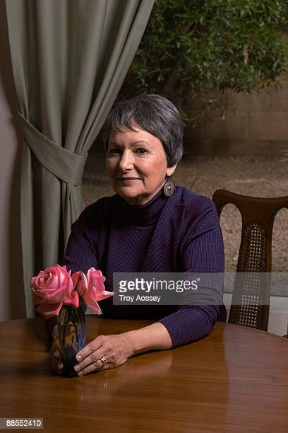 Woman sitting at table with floral arrangement