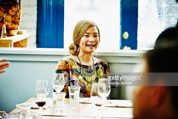 Woman sitting at table with friends in restaurant