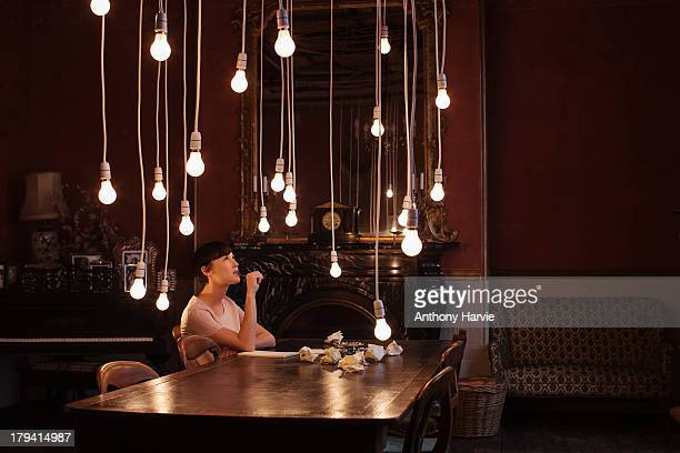 woman sitting at table with hanging lightbulbs - vorstellungskraft stock-fotos und bilder