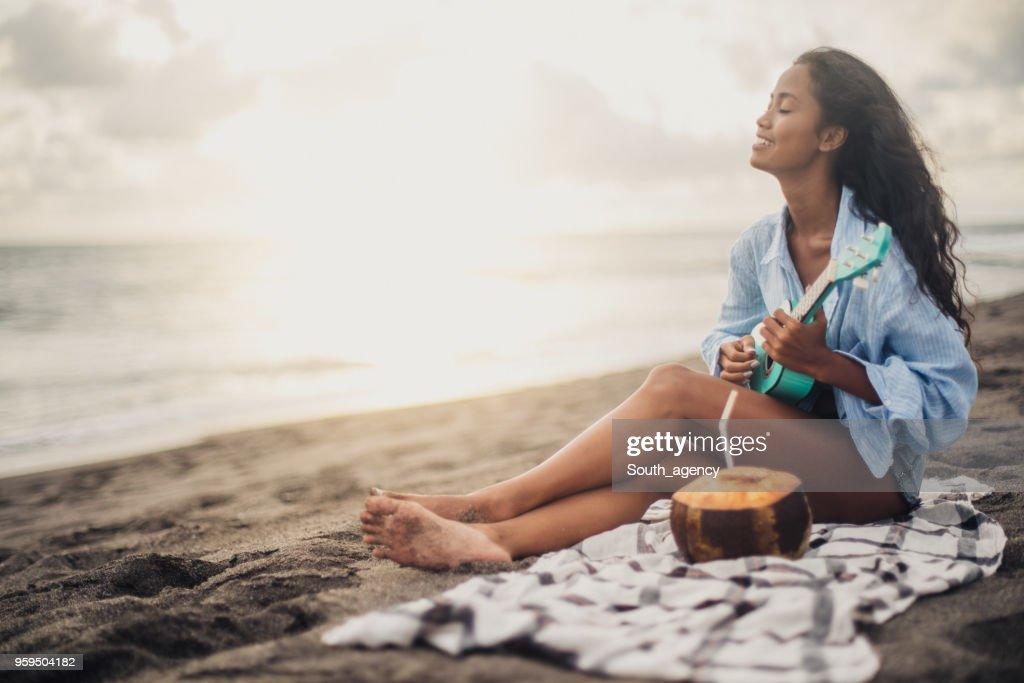 Frau am Strand sitzen und spielen der ukulele : Stock-Foto