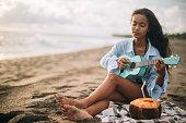 woman sitting at beach playing ukulele