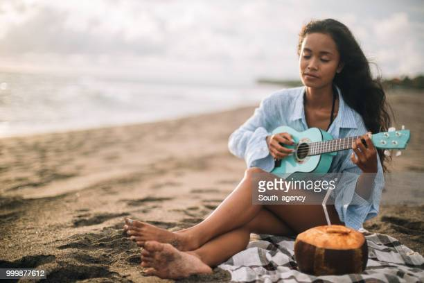 Woman sitting at the beach and playing ukulele