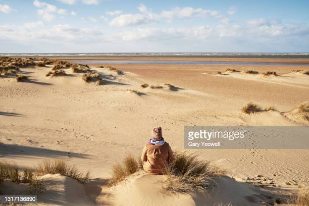 woman sitting at the beach - headwear stock pictures, royalty-free photos & images