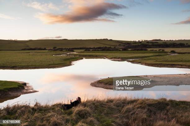 Woman sitting at the edge of a pond during sunset