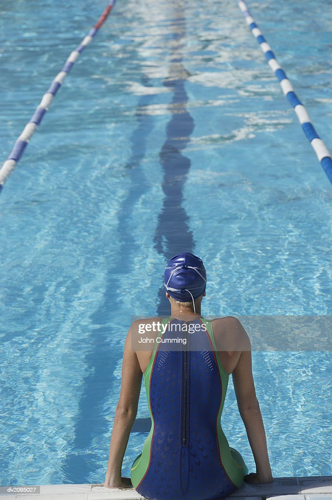 Woman Sitting at the Edge of a Swimming Pool : Stock Photo