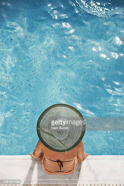 woman sitting at the edge of pool - sun hat stock pictures, royalty-free photos & images