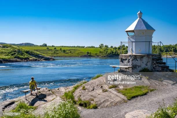 woman sitting at the edge of the water at saltstraumen near bodø in northern norway. saltstraumen lighthouse - finn bjurvoll stock-fotos und bilder