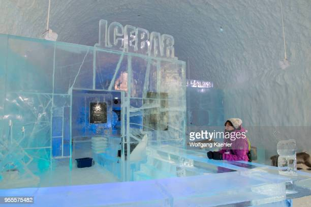 A woman sitting at the Icebar at the ICEHOTEL 365 which was launched in 2016 and is a permanent structure offering year round the stay in the...