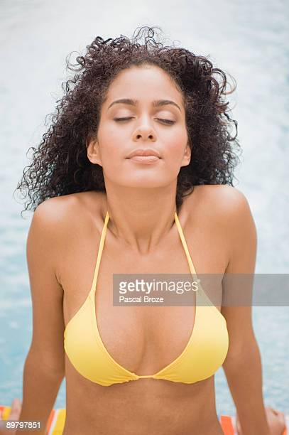 Woman sitting at the poolside with her eyes closed