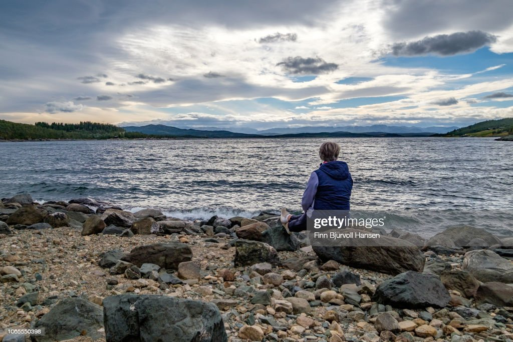 Woman sitting at the seashore looking into to the sunset : Stock Photo