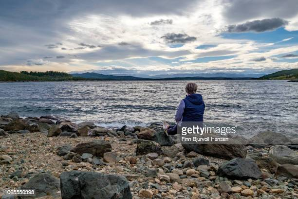 woman sitting at the seashore looking into to the sunset - finn bjurvoll stock pictures, royalty-free photos & images
