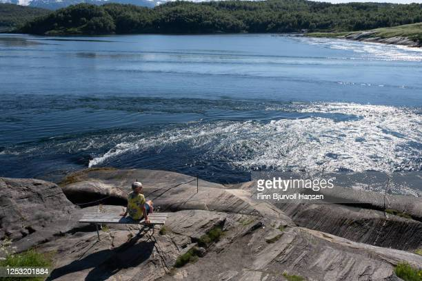 woman sitting at the waters edge at saltstraumen near bodø in northern norway - finn bjurvoll stock-fotos und bilder