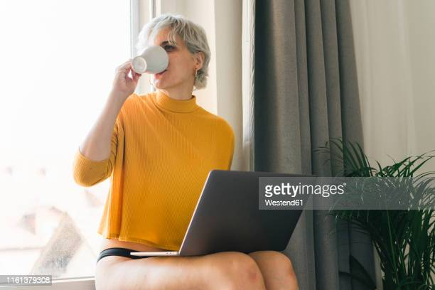 woman sitting at the window at home with laptop drinking coffee from cup - frau in slip stock-fotos und bilder