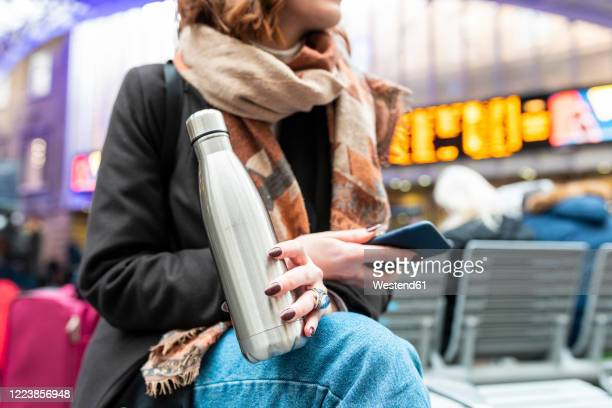 woman sitting at train station with thermos flask and mobile phone - railway station stock pictures, royalty-free photos & images