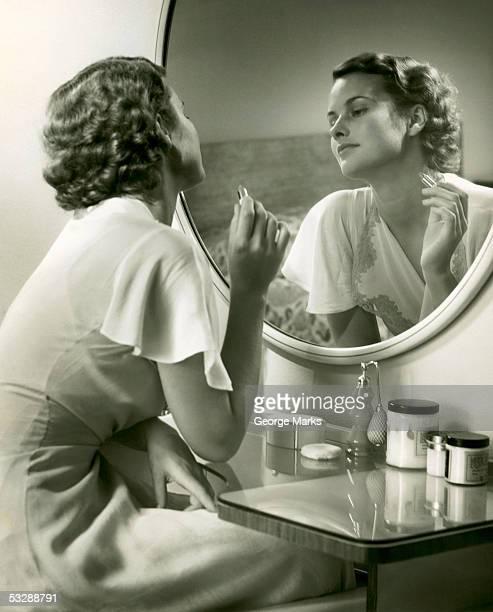 Woman sitting at vanity and staring at r