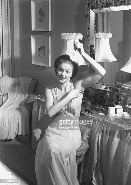 Woman sitting at vanity table, applying cosmetics, (B&W)