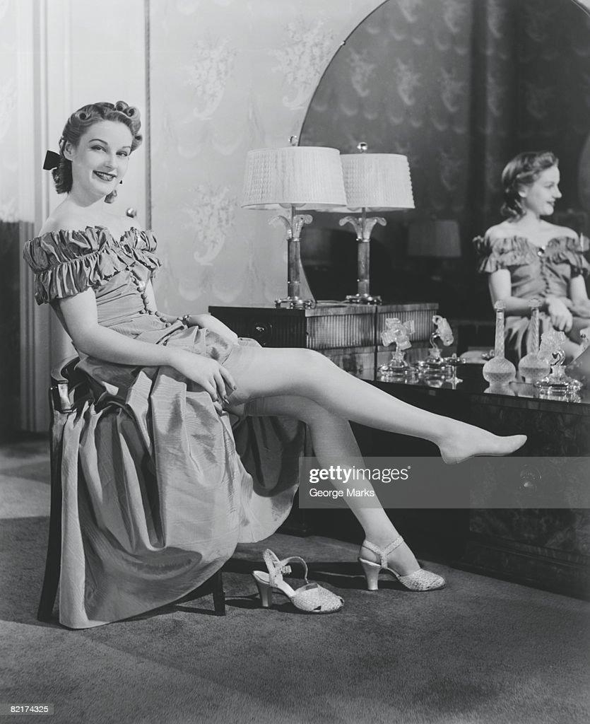 Woman Sitting At Vanity Table Putting On Stockings
