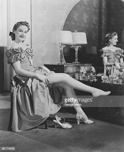 Woman sitting at vanity table, putting on stockings, (B&W), portrait