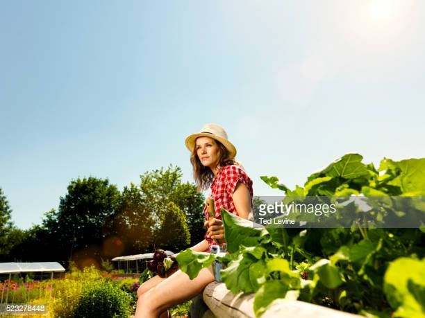Woman sitting at wooden truss in garden, Bavaria, Germany