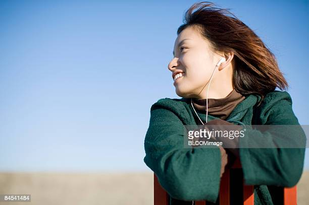 Woman sitting back to front on chair, listening to music, outdoors