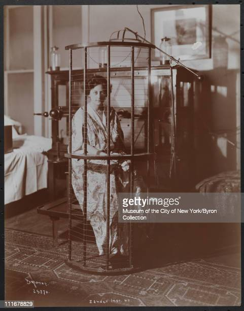 Woman sitting behind a cagelike contraption at the Zander Institute where therapeutic exercise was carried out by means of special apparatus New York...