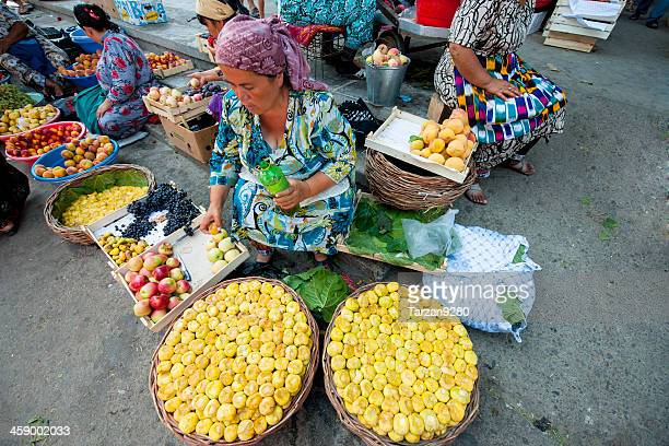 woman sitting behind her fruit stand - oezbekistan stockfoto's en -beelden