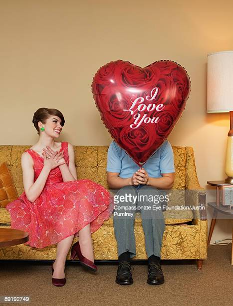 woman sitting beside man with heart-shaped balloon
