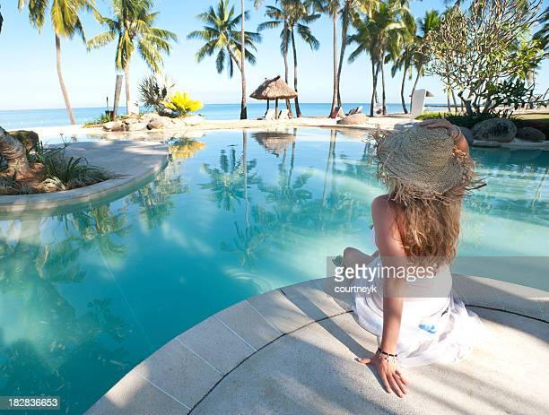 Woman sitting beside the pool with ocean in background
