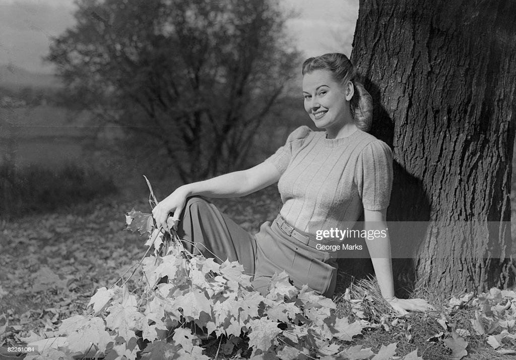 Woman sitting beside tree, portrait : Stock Photo