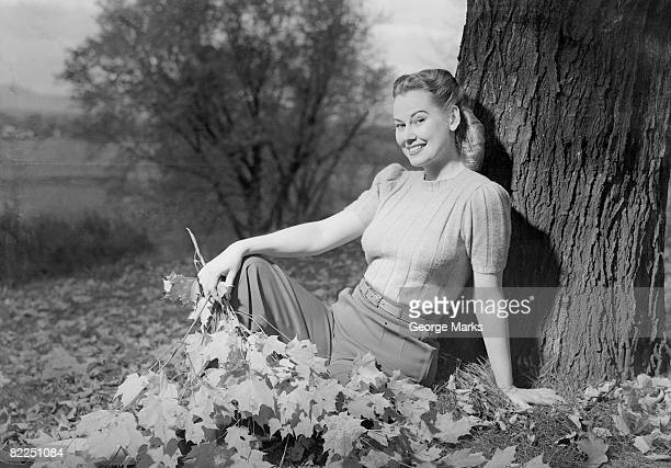 Woman sitting beside tree, portrait