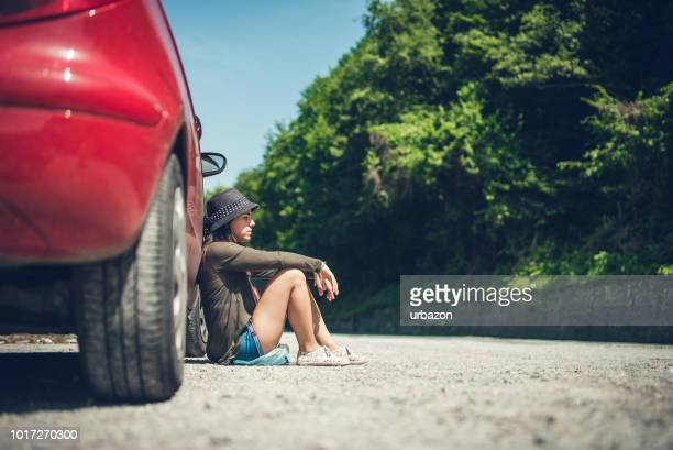 woman sitting by a broken down car - stranded stock photos and pictures