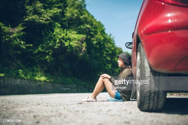 woman sitting by a broken down car - bad luck stock pictures, royalty-free photos & images