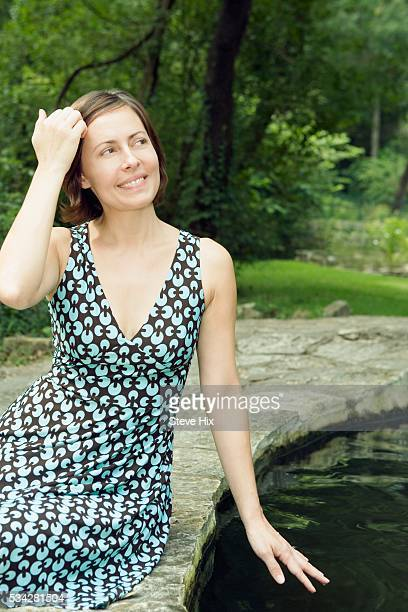 Woman Sitting by a Pool of Water