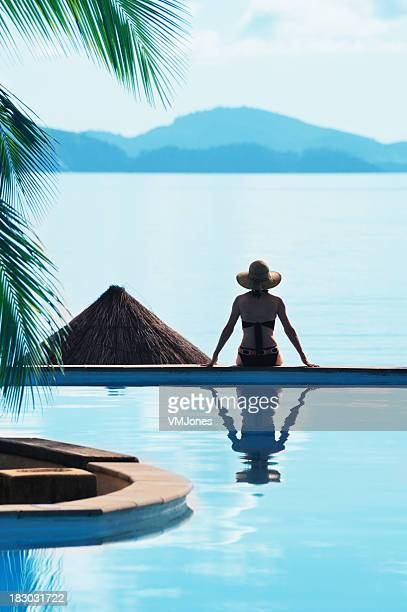 Woman Sitting by a Pool Tropical Setting