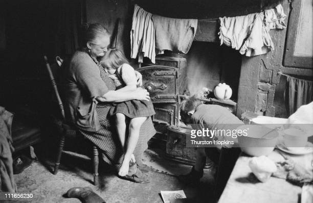 A woman sitting by a stove with two children at their home in the Frank Street slum clearance area of Liverpool 19th November 1956 Original...