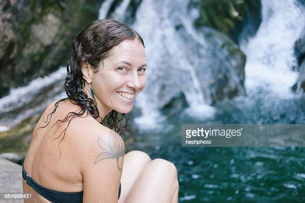 a woman sitting by a swimming hole in woods with waterfall - heshphoto stock pictures, royalty-free photos & images