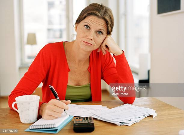 a woman sitting by a table. - one mid adult woman only stock pictures, royalty-free photos & images