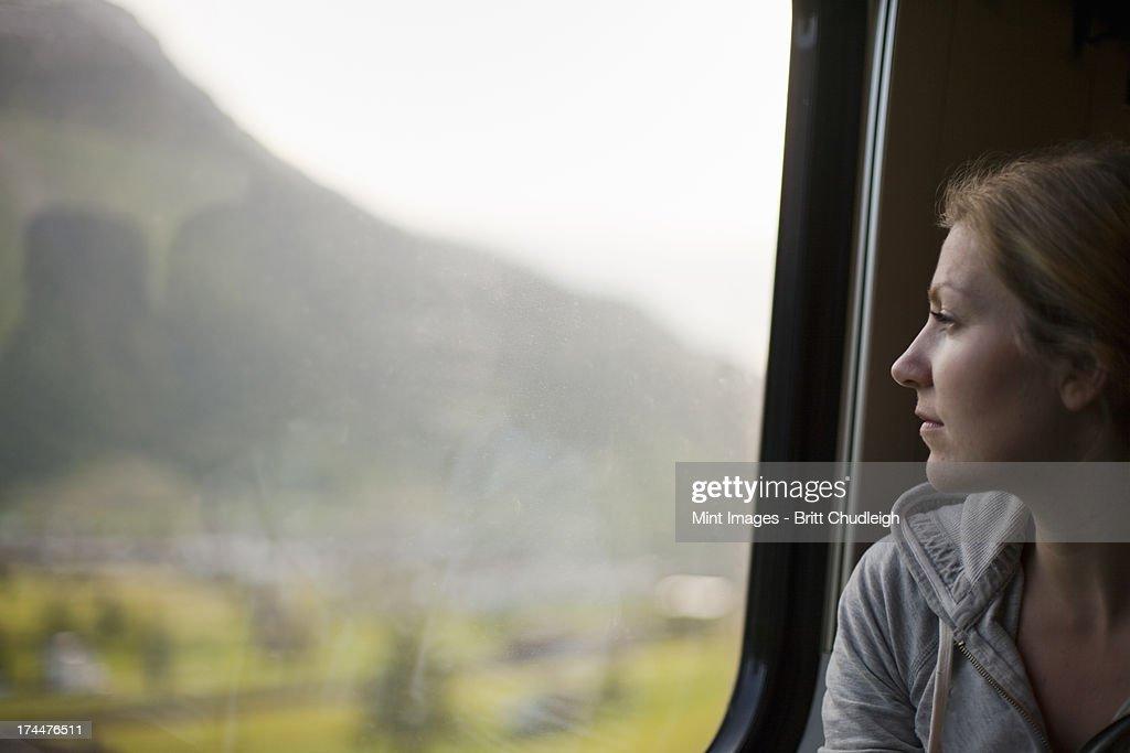 Eine Frau sitzt mit einem Zug Fenster mit Blick auf die : Stock-Foto