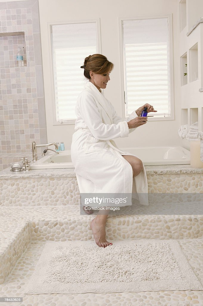 Woman sitting by baht tub in bathrobe : Stockfoto
