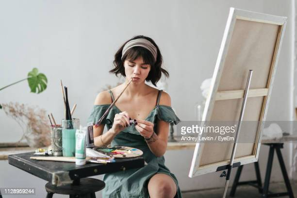 woman sitting by easel against wall - くわえる ストックフォトと画像