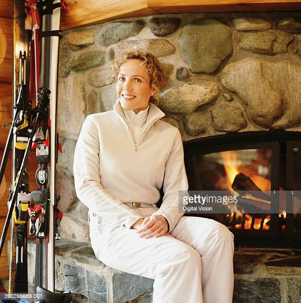 Woman sitting by fireside, smiling, portrait